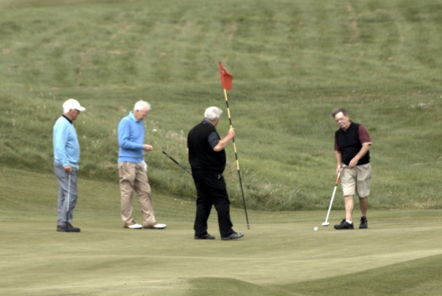 John McArthur holds the flag as others try to match his birdie on the 14th.